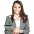 Business woman asian office gesture attractive standing holding in positive beautiful young pretty model tablet smiling dress suit Royalty Free Stock Photo