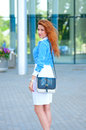 Business woman with bag in front of office building womanwith red hair Royalty Free Stock Photography