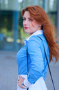 Business woman with bag in front of office building womanwith red hair Royalty Free Stock Photos