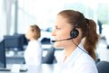 Business woman beautiful young female call center operator with headset in office Stock Photography