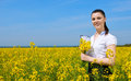 Business woman with bouquet and clipboard relaxing in flower field outdoor. Young girl in yellow rapeseed field. Beautiful spring Royalty Free Stock Photo