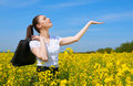 Business woman with briefcase show palm to sun. Young girl in yellow flower field. Beautiful spring landscape, bright sunny day, r Royalty Free Stock Photo