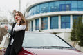 Business woman with car keys laptop and cell phone standing near her Stock Images
