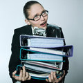 Business woman carrying files and folders studio shot portrait of one caucasian young businesswoman wearing heavy Royalty Free Stock Photo