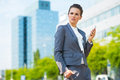 Business woman with cell phone in modern office district into the ultra trends Stock Images