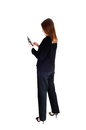 Business woman on cell phone a tall slim young standing in a black suit from the back dialling the isolated for white background Royalty Free Stock Image