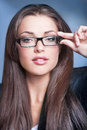 Business woman close up portrait of beautiful young in glasses on dark blue background Royalty Free Stock Image