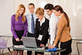 Business woman with colleagues looking at laptop young beautiful women smiling a in front of her and her people around her Royalty Free Stock Photo