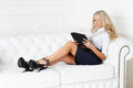 Business woman with computer tablet young sits on the white sofa Royalty Free Stock Photography