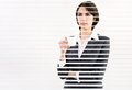 Business woman with cup of coffe looking through a venetian blind in an office Royalty Free Stock Photos