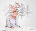 Business woman at desk with labyrinth and arrow in the background Royalty Free Stock Photos