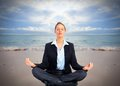 Business woman doing yoga on the beach. Royalty Free Stock Photo