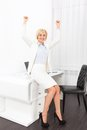 Business woman excited hands up raised arms hold fist sitting at modern office desk surprised happy smile businesswoman success Stock Photos