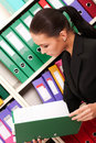 Business woman in front of shelves with folders Stock Image
