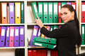 Business woman in front of shelves with folders Stock Photos