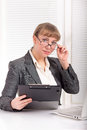 Business woman with glasses dressed in a formal suit sitting at her desk Royalty Free Stock Images