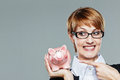 Business woman with glasses smiling and pointing finger to her piggy bank isolated on grey Royalty Free Stock Photos