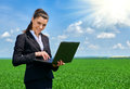 Business woman in green grass field outdoor work on laptop. Young girl dressed in black suit. Beautiful spring landscape with clou Royalty Free Stock Photo