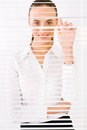 Business woman happy peeking through a venetian blind in an office Stock Image
