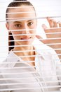 Business woman happy peeking through a venetian blind in an office Royalty Free Stock Images