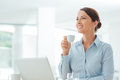 Business woman having a coffee break attractive smiling sitting at office desk holding cup of she is relaxing and looking away Stock Images
