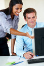 Business woman helping a colleague on a computer Stock Photo