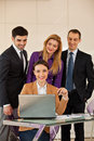 Business woman with her team young beautiful women smiling a laptop in front of and three colleagues people in the back Royalty Free Stock Photos