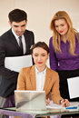 Business woman with her team young beautiful women smiling looking at laptop and two colleagues people in the back Royalty Free Stock Images