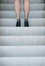 Business woman in high heels standing on escalator outdoors Stock Image