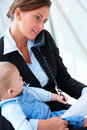 Business woman holding a baby talking on phone Stock Photos