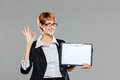 Business woman holding a clipboard and gesturing on grey Royalty Free Stock Photo