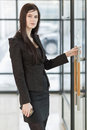 Business woman holding the door handle in suit Stock Images