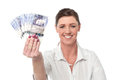 Business woman holding fan of currency notes showing british pound isolated Stock Images