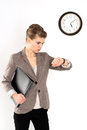 Business woman in hurry looking at her watch isolated over white background young female executive standing with black folder Stock Photo