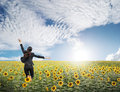 Business woman jumping in blue sky over sunflowers field Royalty Free Stock Photo