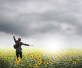 Business woman jumping in rainclouds over sunflowers field Royalty Free Stock Photo