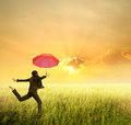 Business woman jumping to sunset with red umbrella Stock Images