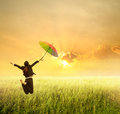 Business woman jumping to sunset with red umbrella Stock Photography