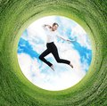Business woman jumps in rotated field with green grass. Royalty Free Stock Photo