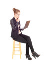 Business woman with laptop sitting a young blond on a chair working on her in black tights and jacket isolated for white Stock Photo