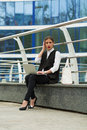 Business woman with a laptop working outside in front of businnes center building Stock Image