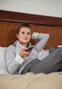 Business woman laying on bed and watching tv in hotel room Stock Image