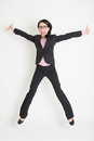 Business woman leaping high in the air full length of asian successful on plain background Stock Images