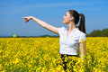 Business woman looking into the distance and point. Young girl in yellow flower field. Beautiful spring landscape, bright sunny da Royalty Free Stock Photo