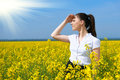 Business woman looking into the distance. Young girl in yellow flower field. Beautiful spring landscape, bright sunny day, rapesee Royalty Free Stock Photo