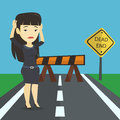 Business woman looking at road sign dead end.