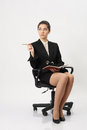 Business woman with a notebook and pencil in hand sitting chair looking away Stock Photo