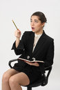 Business woman with a notebook and pencil in hand surprised at the top indicates the sitting an office chair on white Royalty Free Stock Image