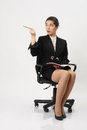 Business woman with a notebook and pencil in hand surprised at the top indicates the sitting an office chair on white Royalty Free Stock Photos