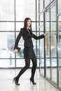 Business woman with a notepad enters door beautiful the glass Royalty Free Stock Image